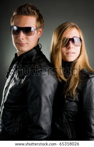 couple with leather jackets and sunglasses - stock photo