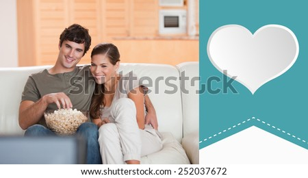 Couple with popcorn on the sofa watching a movie against heart label - stock photo