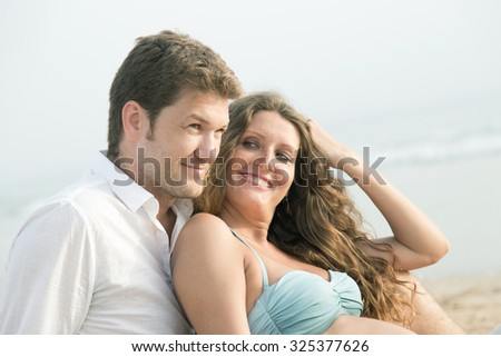 couple with pregnant belly in the beach