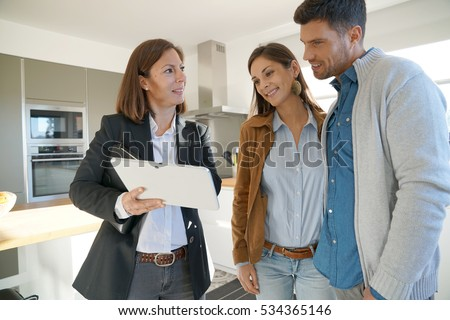 Couple with real-estate agent visiting house for sale