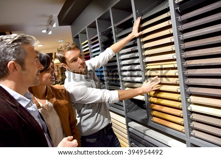 Couple with salesman in kitchen furniture store - stock photo