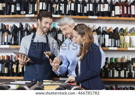 Couple With Salesman Reading Label On Wine Bottle