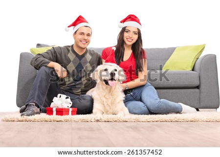 Couple with Santa hats sitting with a dog by a sofa isolated on white background - stock photo
