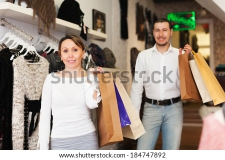 Couple with shop-bags at clothing boutique