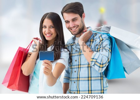 Couple with shopping bags and credit card against blurry christmas tree in room - stock photo