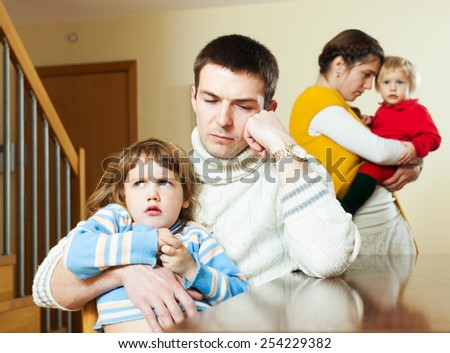 Couple with small children in quarrel at home - stock photo