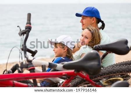 Couple with son sitting on sand with bicycles at seashore - stock photo