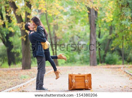 Couple with suitcase kissing at alley in the park - stock photo