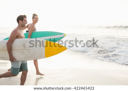 Couple with surfboard running on the beach on a sunny day - stock photo