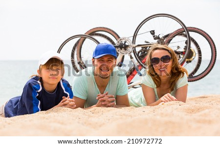 Couple with teenager son lying at seashore in summer day with cycles behind  - stock photo
