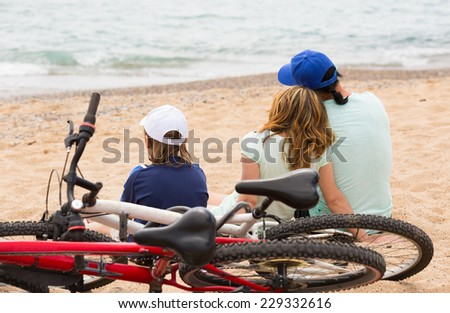 Couple with teenager son sitting at seashore with cycles behind  - stock photo