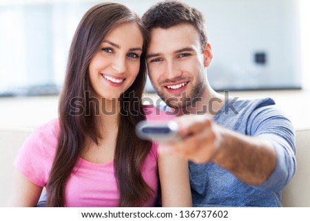 Couple with TV remote  - stock photo