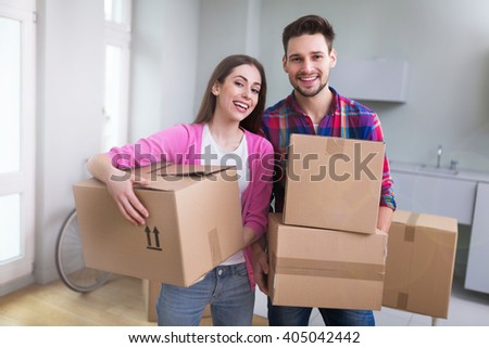 Couple with unpacked boxes in new home - stock photo