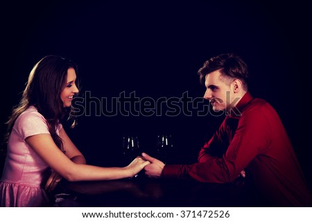 Couple with wine by a table. - stock photo