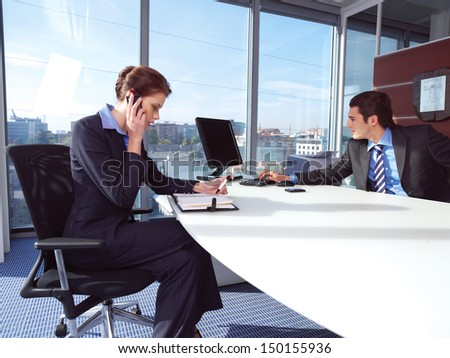 Couple working on laptop computer at office. Woman calling on mobile phone. - stock photo