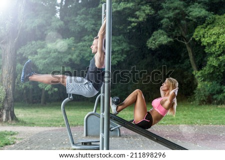 Couple working out on outdoor gym, horizontal - stock photo