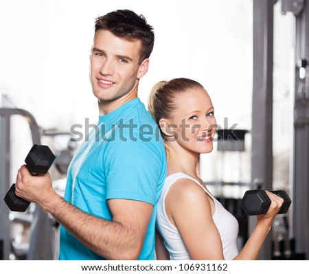 Couple working out with dumbbells - stock photo