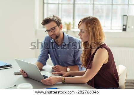 Couple working together in an office sitting at a laptop computer reading the screen with serious expressions - stock photo