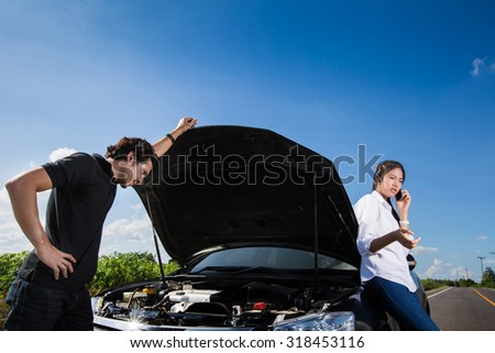 Couples broken car on the way Who's telephone call insurance. ask for help - stock photo