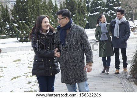 Couples in park covered in snow