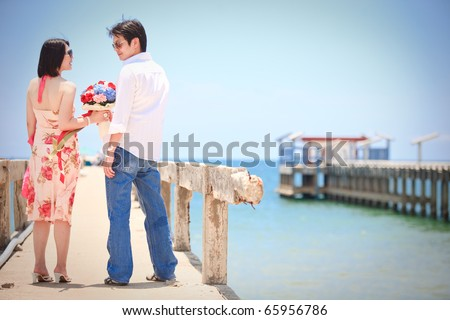 couples make eye contact at pier on the beach - stock photo