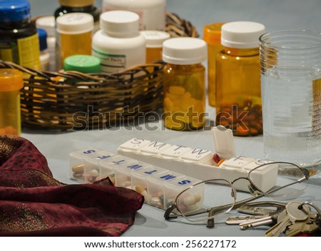 couples multi-day pill organizers with bottled prescriptions - stock photo