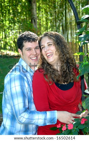 Couples that laugh together stay together.  This couple share an amusing joke in a garden.  She is wearing red and he has on blue. - stock photo