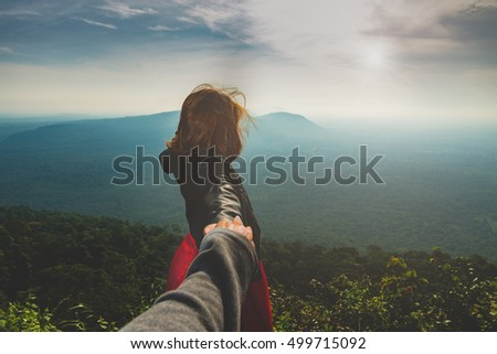 couples, tourists,woman holding hand of her boyfriend while walking on mountain,Couple enjoying a hike in nature concept.
