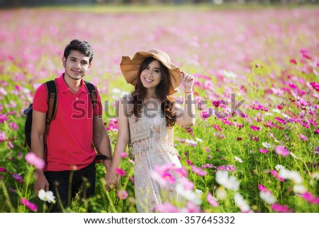 Couples traveling to Cosmos flowers garden in valentines day concept - stock photo