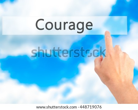 Courage - Hand pressing a button on blurred background concept . Business, technology, internet concept. Stock Photo