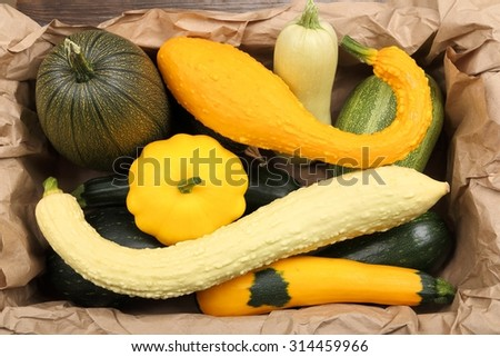 Courgettes and squashes stacked in a box on a paper. - stock photo