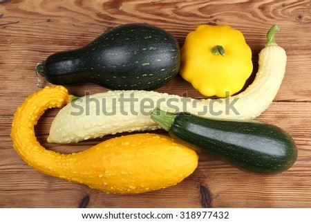 Courgettes and squashes stacked on a wooden table. - stock photo