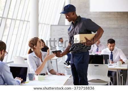 Courier Collecting Package From Businesswoman In Busy Office - stock photo