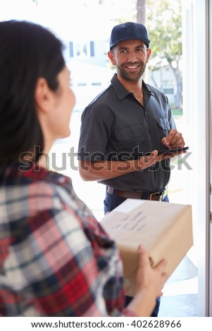 Courier Collecting Package From Woman At Home - stock photo