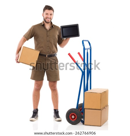 Courier holding a digital tablet. Smiling delivery man standing with package under his arm and showing a digital tablet. Full length studio shot isolated on white. - stock photo