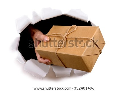 Courier or delivery man delivering mail package through torn white paper background - stock photo