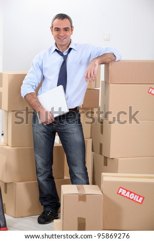 Courrier stood by stacked boxes - stock photo