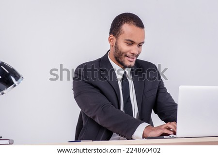 Courteous businesswoman. Smiling African businessman sitting at the table and typing a business plan on a laptop while a businessman sitting at a desk and smiling at the camera on a gray background - stock photo