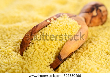 Couscous in a wooden spoon on a background of couscous. Selective focus. - stock photo
