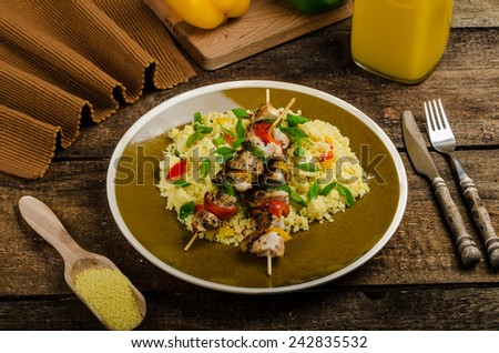 Couscous with vegetables and spring onion, chicken skewer with peppers - stock photo