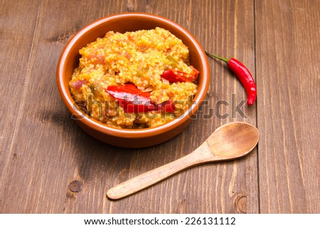 Couscous with vegetables on a bowl on wooden table - stock photo