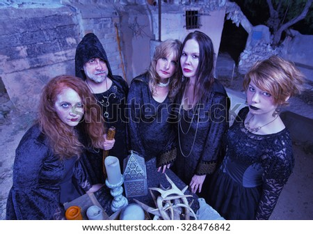 Coven of witches next to altar with antlers