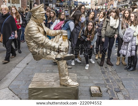 Covent Garden, London, UK - April 11, 2014 : Living statue street performer amazing the crowds by appearing to balance unsupported whilst drinking a beer. - stock photo