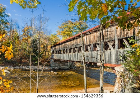 Covered Bridge and Fall Foliage under Blue Sky - stock photo