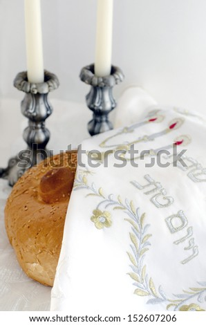 Covered challah bread for the Jewish observance of Shabbat with candles in the background. - stock photo