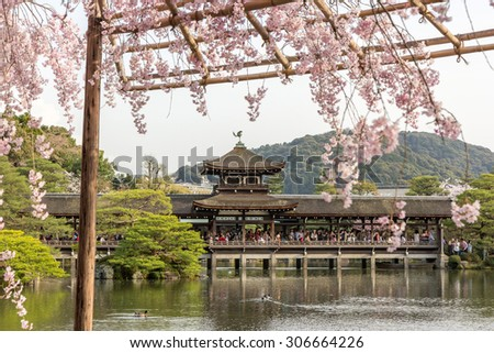 covered japanese bridge over lake in garden behind the main building of heian shrine with out