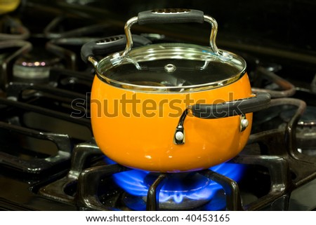 Covered non stick sauce pan on a stove top with fire is turned on - stock photo