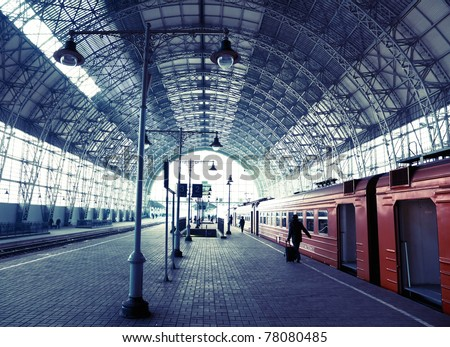 Covered old railway station with train and silhouettes of people - stock photo