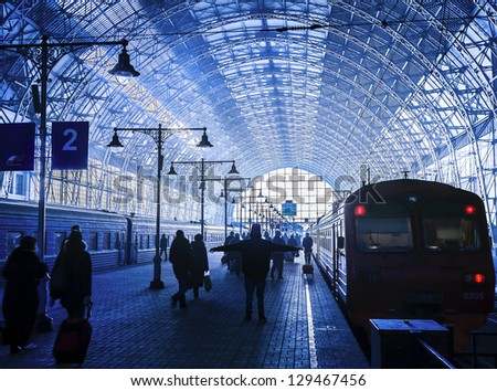 Covered railway station with trains and silhouettes of hurrying people - stock photo
