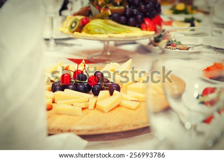 Covered table in the restaurant - cheese plate, fruit plate - stock photo